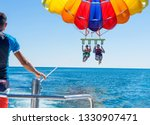 Happy couple parasailing near...