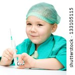 Cute little girl is playing doctor with syringe, isolated over white - stock photo