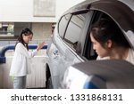 Small photo of Asian girl help waving a car for her mother to reverse in parking car,her mother drove carefully