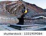 Small photo of Hindu temple, Muktinath Mandir, surrounded by high Himalayan mountains, Annapurna Circuit Trek, Nepal. Buddha statute with orange ribbon looking at the mountains. Sacred place, pilgrimage destination