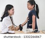 Asian dooctor examining a...