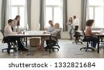 Small photo of Busy multicultural enterprise employees sitting at desks working on computers in modern office rush, staff business people company workers moving talking in big corporate coworking open space room