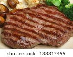 Juicy sirloin steak with vegetables. Shallow DoF. - stock photo