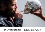 Small photo of Man smoking cigarette near human skull symbol of death. Harmful habits. Destroy your health. Smoking is harmful. Habit to smoke tobacco bring harm to your body. Smoking cause health damage and death.