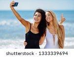 two young women taking selfie... | Shutterstock . vector #1333339694