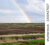 Small photo of Rainbow, a view of the landscape in the field. Formation of the rainbow after the rain. Refraction of light and expansion in terms of spectra.