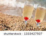 Champagne Glasses On Beach At...