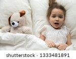 Small photo of Scared frightened little kid girl looking at camera lying in bed on pillow with toy afraid of nightmare, terrified child awaking from bad dream sleep feeling fear disturbed by scary monster, top view
