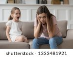Small photo of Stressed exhausted mother looking at camera feeling desperate about screaming stubborn kid daughter tantrum, upset annoyed mom tired of naughty difficult child girl misbehave yelling for attention