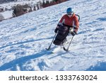 Small photo of disabled person goes mono ski downhill skiing - rehabilitation and winter snow sports, handicapped athlete, slalom , Wheelchair Wandering