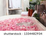 Stock photo bath tub with flower petals filling with water organic spa relaxation in luxury bali outdoor 1334482934