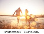 happy couple running on the... | Shutterstock . vector #133463087
