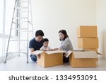 family unpacking boxes in new... | Shutterstock . vector #1334953091