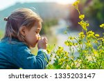 little boy enjoying flowers... | Shutterstock . vector #1335203147