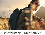 female hiker sitting on a grass ... | Shutterstock . vector #1335358277