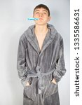 Teenage caucasian boy cleaning his teeth in the morning wearing a dressing gown - stock photo