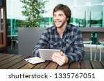happy cheerful young man using...   Shutterstock . vector #1335767051