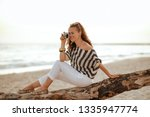 smiling stylish woman in white pants and striped blouse taking photos with retro photo camera while sitting on a wooden snag on the seashore at sunset.