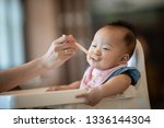 mother feeding her baby with... | Shutterstock . vector #1336144304