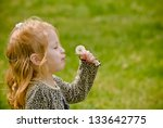 Young girl trying to blow dandelion seeds - stock photo