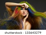 portrait of young beautiful red-haired woman with waving long hair colored with blue green and red - stock photo