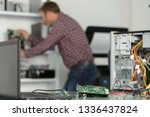 frustrated young man fixing a pc | Shutterstock . vector #1336437824