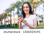 Small photo of Touch of delight. Bodacious girl with long dark hair white smile and perfect body shape is holding her white phone among palm trees full of sun lights and green grass.
