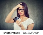 Small photo of Confused stressed woman looking at too many credit cards full of debt
