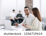 employees sitting at a table in ... | Shutterstock . vector #1336719614