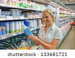 Stock photo a young woman buys milk at the supermarket stands in front of the refrigerated section 133681721