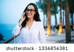 Small photo of The lights of the evening. Bodacious woman in front of flamboyant orange lights on the greeny palms, evening deep blue sky and clear sea water is having a pleasant phone conversation.