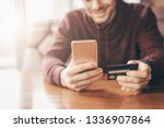 Small photo of Online banking with smart phone, man rewrite a number of credit card