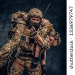 Combat conflict, special mission, retreat. Soldier special forces rescue his wounded teammate carrying him on his shoulders from the battlefield, talking on the radio and calls for support - stock photo