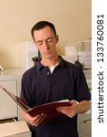 Caucasian male in file room reading papers inside a folder - stock photo
