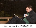 Man drinking coffee and reading a newspaper outside on a cool fall morning - stock photo