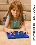 Young female child works on an oversized calculator - stock photo