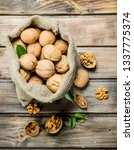 walnuts in a bag . on a wooden... | Shutterstock . vector #1337775374