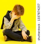 Small photo of The little boy holds his head with his hand. The concept of illness, chagrin. Isolated.