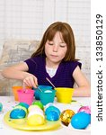 Young girl in the process of coloring Easter Eggs - Step four, the egg nearly submerged into the cup of dye - stock photo