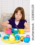 Young girl in the process of coloring Easter Eggs - Step three, lowering the egg partially into the cup of dye - stock photo