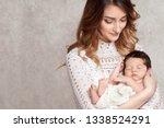 pretty woman holding a newborn...   Shutterstock . vector #1338524291
