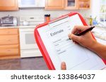 Closeup of a contractors clipboard as he writes up an estimate for a kitchen remodel. Shallow depth of field with focus on clipboard. - stock photo
