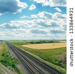 railroads to horizon and cloudy sky - stock photo