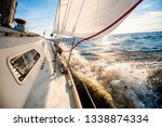 white yacht sailing at sunset.... | Shutterstock . vector #1338874334