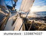 white yacht sailing at sunset.... | Shutterstock . vector #1338874337