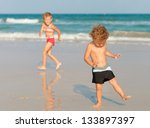 two happy kids playing on beach | Shutterstock . vector #133897397