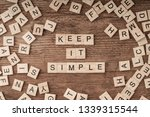 Stock photo keep it simple written with cube letters on wooden background 1339315544