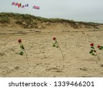 Small photo of red roses in sandy Utah Beach, place of D Day landing and operation Overlord in 1944 during World War 2, touristic place with historical importance in Normandy region, northern France, western Europe