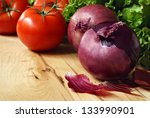 Fresh produce (red onions, tomatoes, and lettuce) on wooden cutting board.  Macro with shallow dof and copy space. - stock photo