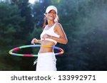 Woman Rotates Hula Hoop On...